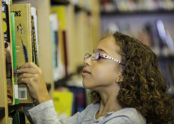 MSP student browsing through books on the library bookshelf