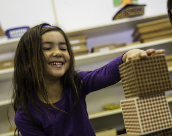 Montessori student stacking blocks