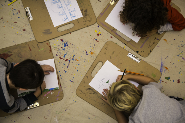 Three MSP students coloring at an after school program