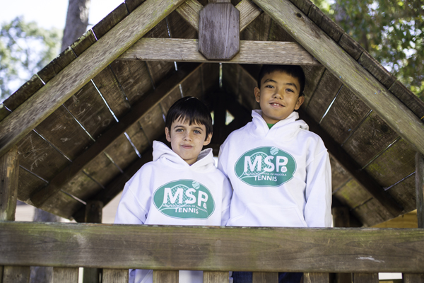 Two MSP students wearing MSP Tennis hoodies on the playground