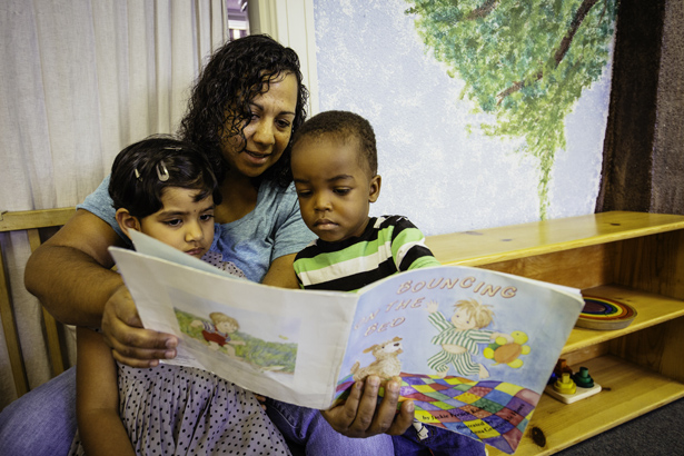 Teacher reading to two MSP students