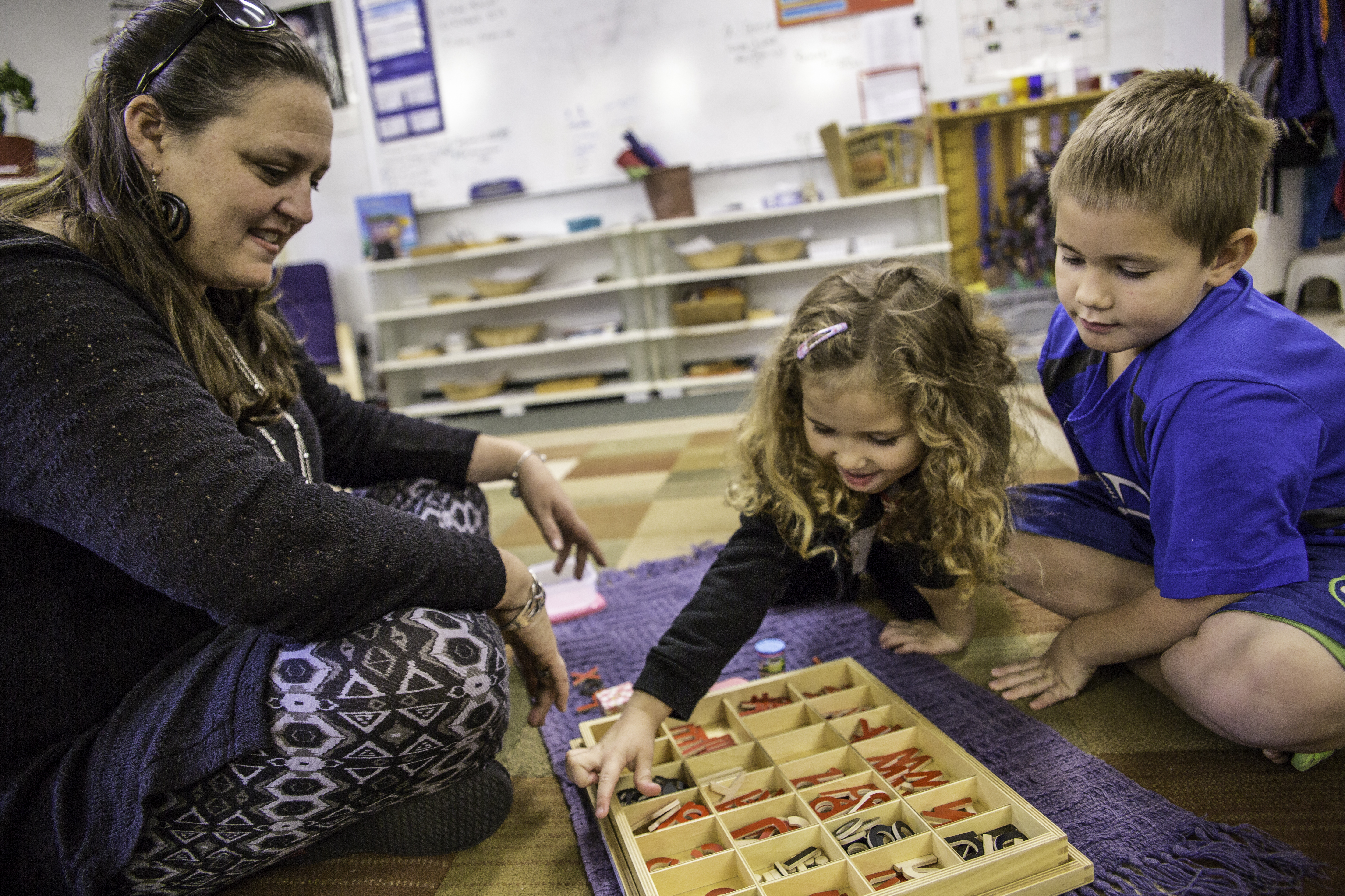 MSP teacher with two students learning the alphabet